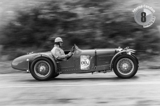 A classic two-seater races up the hill.