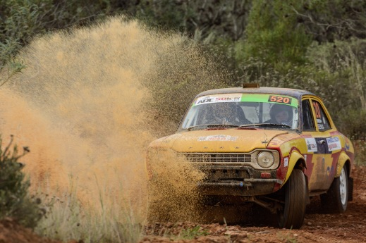 A Ford Escort in rally trim splashes through a mudhole.