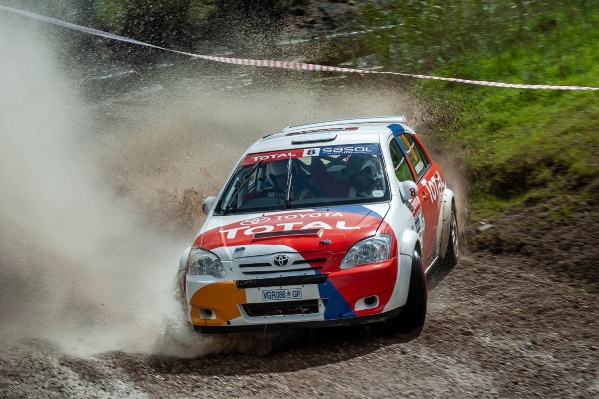 A rally car splashing through water
