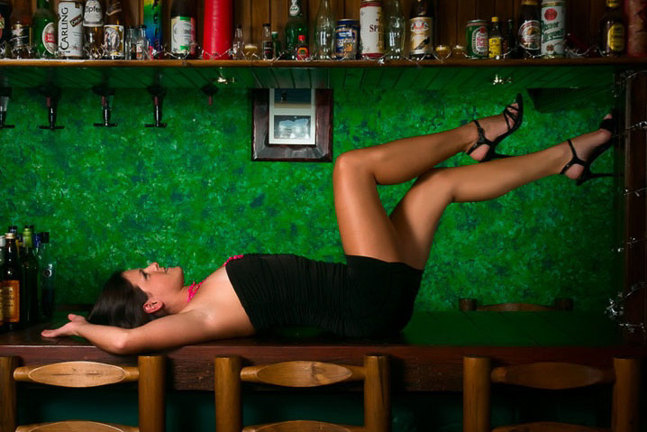 A woman with long legs laying on a bar