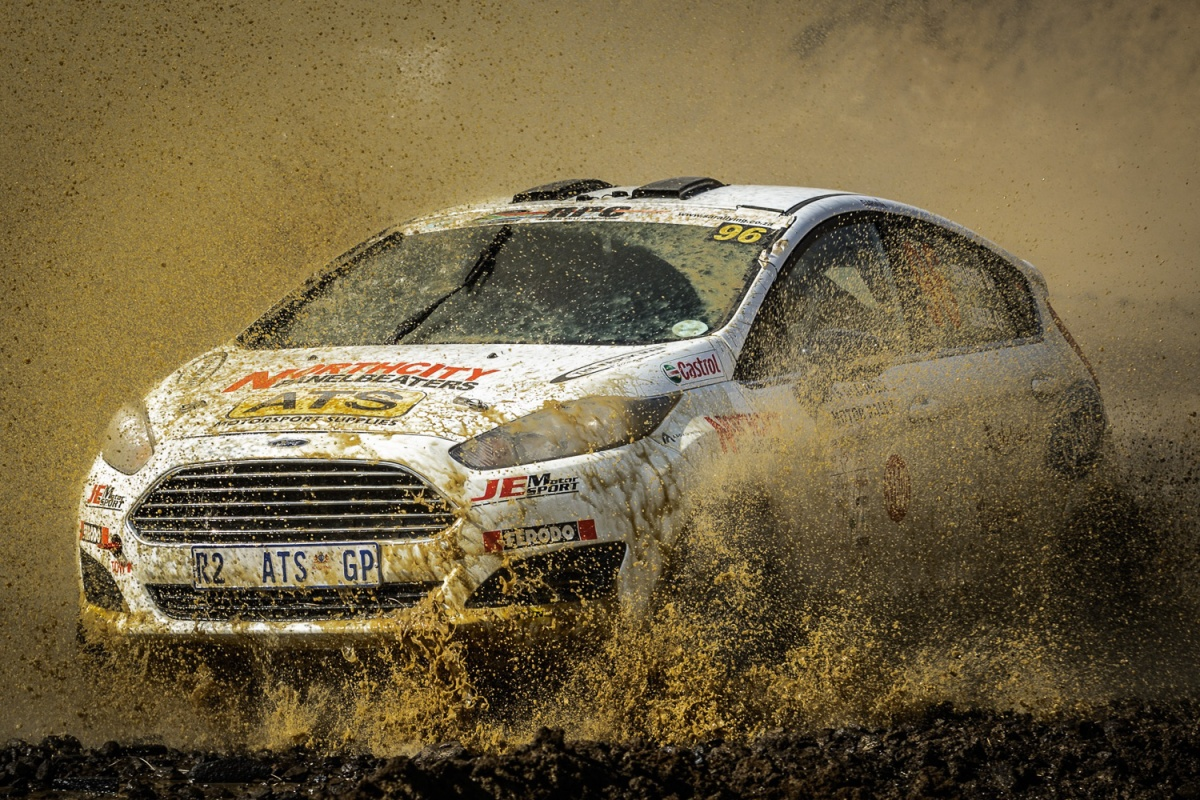 muddy rally car splashing through water
