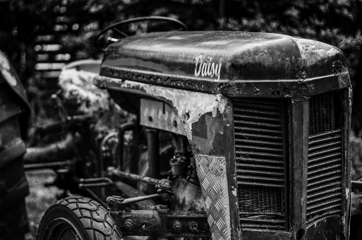 a rusty old tractor in black and white